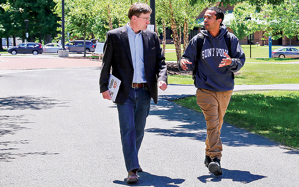 Professor John Marsh walks with student near the Student Center